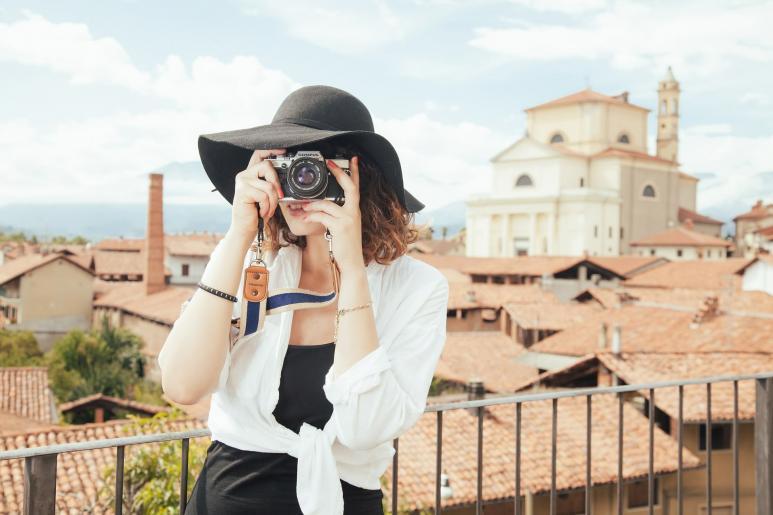 Eine Frau mit Hut steht auf einem Balkon und blickt durch eine Kamera.